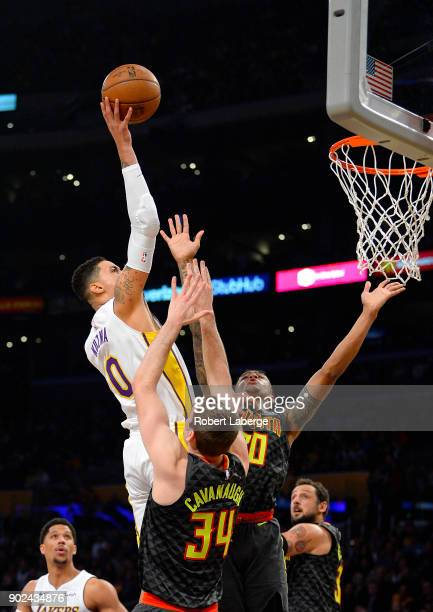 Kyle Kuzma of the Los Angeles Lakers attempts a shot against Tyler Cavanaugh and John Collins of the Atlanta Hawks on January 7 2018 at STAPLES...