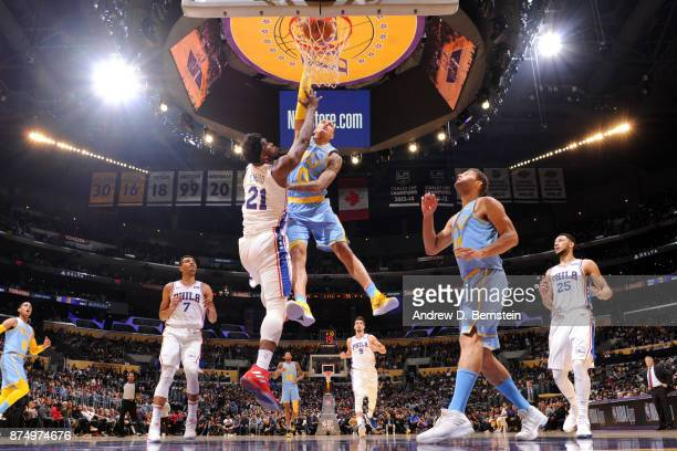 Kyle Kuzma of the Los Angeles Lakers attempts to dunk over Joel Embiid of the Philadelphia 76ers on November 15 2017 at STAPLES Center in Los Angeles...