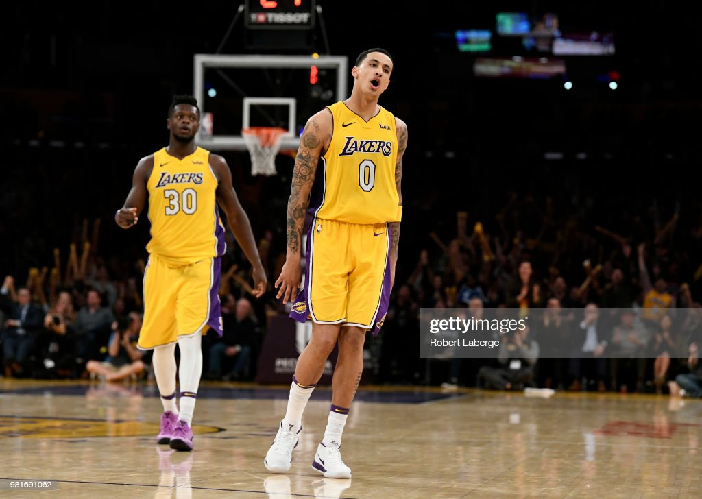 Kyle Kuzma #0 of the Los Angeles Lakers celebrates a shot against the Denver Nuggets as his teamate Julius Randle looks on on March 13, 2018 at STAPLES Center in Los Angeles, California.