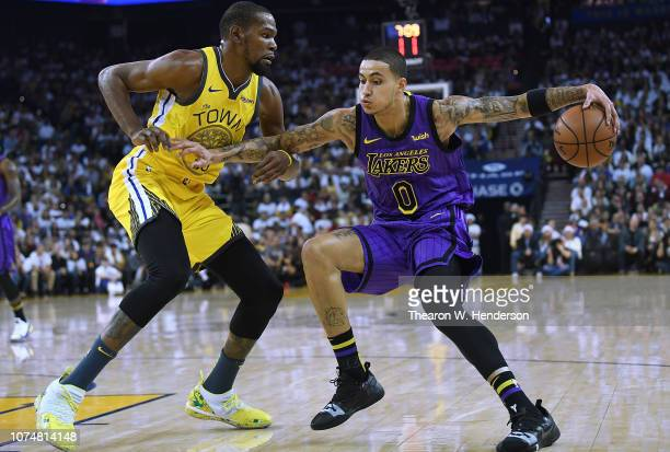 Kyle Kuzma of the Los Angeles Lakers dribbles the ball while being closely guarded by Kevin Durant of the Golden State Warriors during the first half...