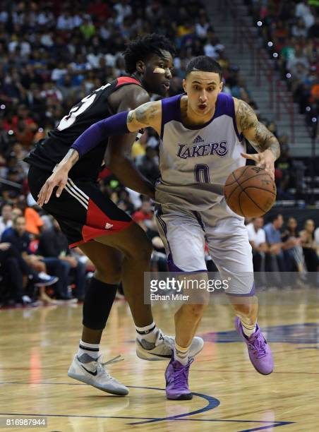 Kyle Kuzma of the Los Angeles Lakers drives past Caleb Swanigan of the Portland Trail Blazers during the championship game of the 2017 Summer League...