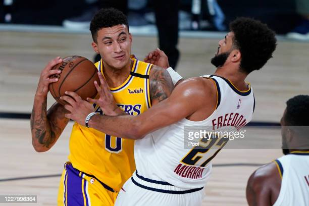 Kyle Kuzma of the Los Angeles Lakers drives to the basket against Jamal Murray of the Denver Nuggets during the second half at The Arena at ESPN Wide...
