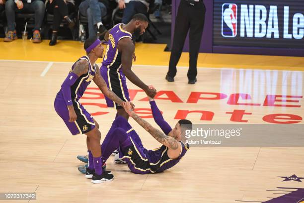 Kyle Kuzma of the Los Angeles Lakers is helped to his feet from team against the San Antonio Spurs on December 5 2018 at STAPLES Center in Los...