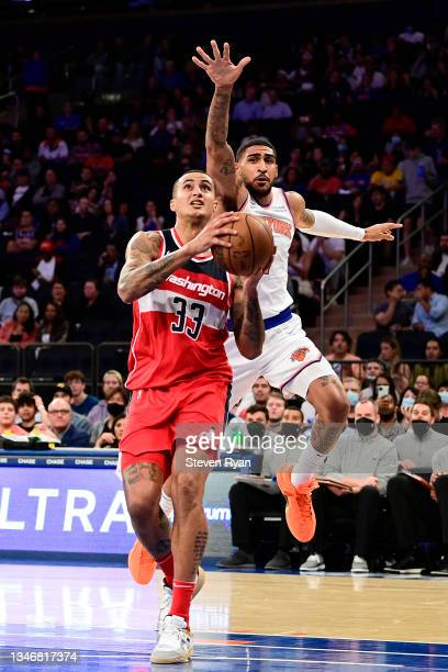 Kyle Kuzma of the Washington Wizards gets past Obi Toppin of the New York Knicks on his way to a dunk during a preseason game at Madison Square...