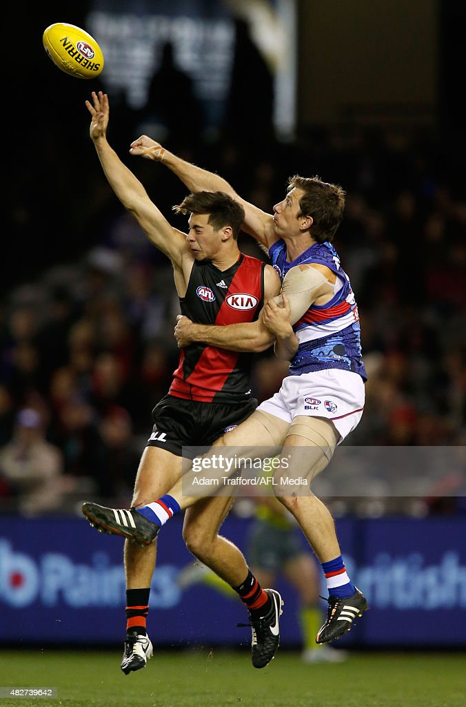 Kyle Langford of the Bombers an Dale Morris of the Bulldogs compete for the ball during the 2015 AFL round 18 match between the Essendon Bombers and the Western Bulldogs at Etihad Stadium, Melbourne, Australia on August 2, 2015.