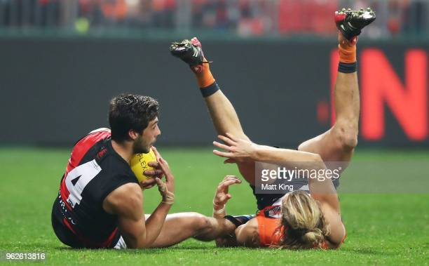 Kyle Langford of the Bombers is challenged by Nick Haynes of the Giants during the round 10 AFL match between the Greater Western Sydney Giants and...