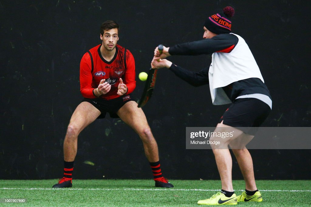 Kyle Langford of the Bombers, sent to hospital after his match on Friday against the Sydney Swans, takes part in a reflex drill when catching a tennis ball hit with a cricket bat by assistant coach James Kelly during an Essendon Bombers AFL training session at The Hangar on July 30, 2018 in Melbourne, Australia.