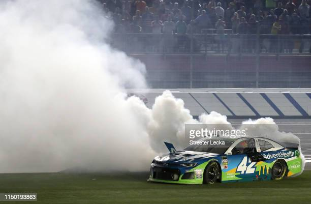 Kyle Larson driver of the Advent Health Chevrolet celebrates with a burnout after winning the Monster Energy NASCAR Cup Series AllStar Race at...