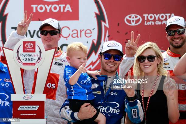Kyle Larson driver of the Credit One Bank Chevrolet his girlfriend Katelyn Sweet and their son Owen pose with the trophy in Victory Lane after...