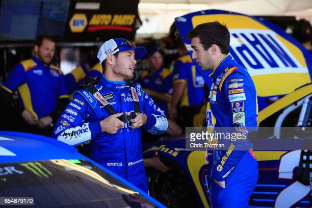 Kyle Larson driver of the Credit One Bank Chevrolet talks with Chase Elliott driver of the NAPA Chevrolet in the garage during practice for the...