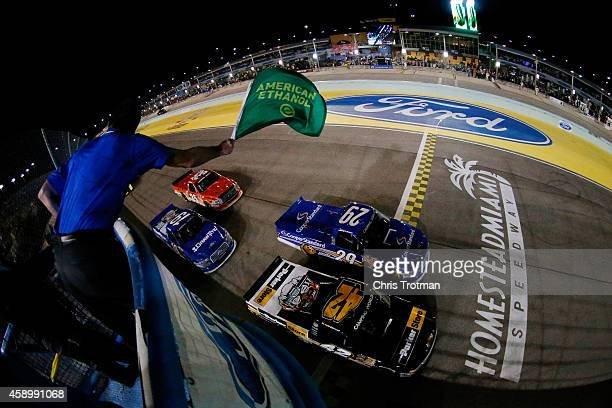 Kyle Larson driver of the ParkerStore Chevrolet and Ryan Blaney driver of the Cooper Standard Ford lead the field past the green flag to start during...