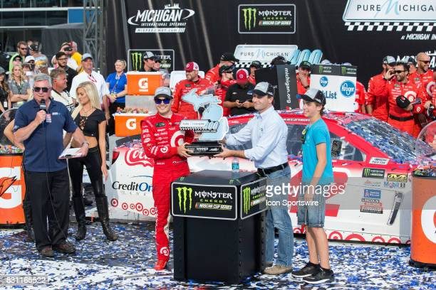 Kyle Larson driver of the Target Chevrolet accepts the winner's trophy after winning the Monster Energy NASCAR Cup Series Pure Michigan 400 race on...
