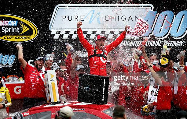 Kyle Larson driver of the Target Chevrolet celebrates in victory lane after winning the NASCAR Sprint Cup Series Pure Michigan 400 at Michigan...