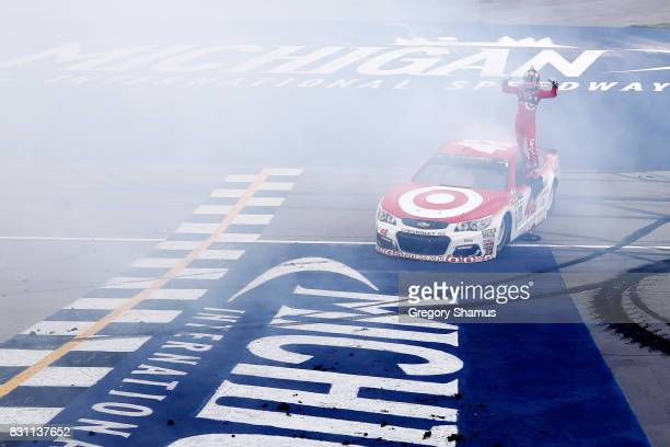 Kyle Larson driver of the Target Chevrolet celebrates winning the Monster Energy NASCAR Cup Series Pure Michigan 400 at Michigan International...