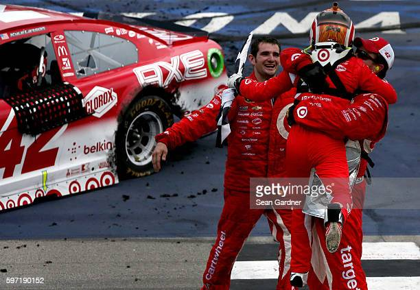 Kyle Larson driver of the Target Chevrolet celebrates with crew members after winning the NASCAR Sprint Cup Series Pure Michigan 400 at Michigan...