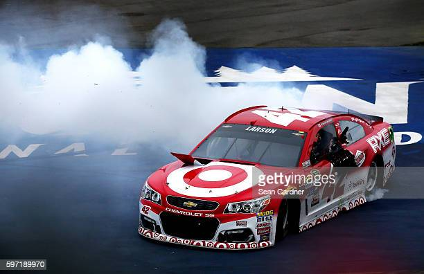 Kyle Larson driver of the Target Chevrolet does a burnout after winning the NASCAR Sprint Cup Series Pure Michigan 400 at Michigan International...