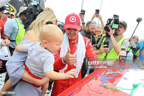 Kyle Larson driver of the Target Chevrolet girlfriend Katelyn Sweet and son Owen Larson affixe the winner's decal to his car in Victory Lane after...