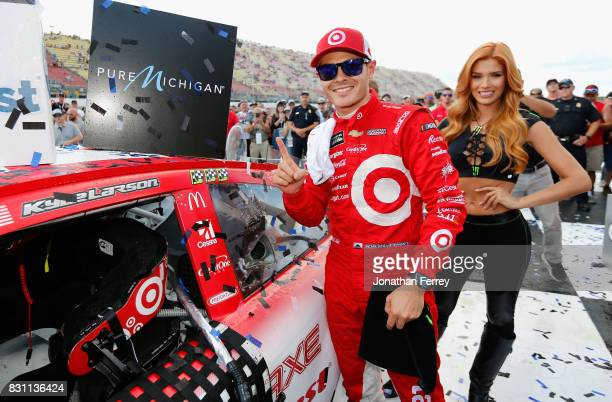 Kyle Larson driver of the Target Chevrolet poses with the winner's decal after winning the Monster Energy NASCAR Cup Series Pure Michigan 400 at...