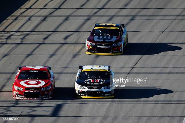 Kyle Larson driver of the Target Chevrolet races Kevin Harvick driver of the Jimmy John's Chevrolet in front of Jeff Gordon driver of the Drive To...