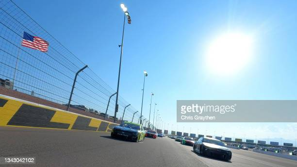 Kyle Larson, driver of the Tarlton and Son Chevrolet, and Ryan Blaney, driver of the Ford, lead the field on a pace lap prior to the NASCAR Cup...