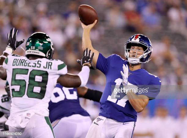 Kyle Lauletta of the New York Giants throws a touchdown pass in the fourth quarter as James Burgess of the New York Jets defends during a preseason...