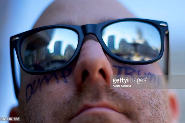 Kyle Lloyd wears face painting of DUMP TRUMP joining more than a thousand protesters in a march to Independence Hall against Presidentelect Donald...