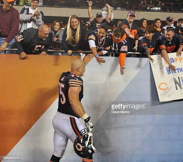 Kyle Long of the Chicago Bears high fives the fans after the Bears victory on October 10 2013 at Soldier Field in Chicago Illinois The Chicago Bears...