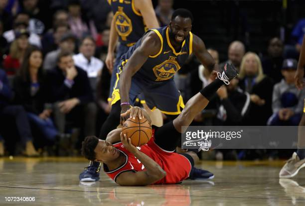 Kyle Lowry of the Toronto Raptors and Draymond Green of the Golden State Warriors go for a loose ball at ORACLE Arena on December 12 2018 in Oakland...