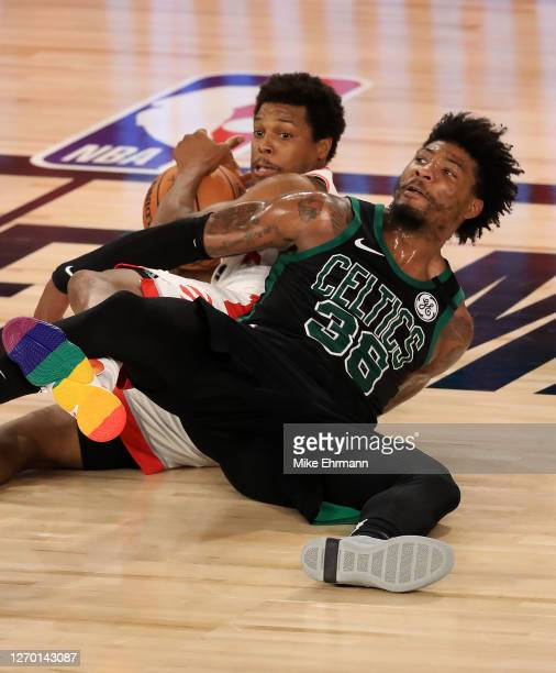 Kyle Lowry of the Toronto Raptors and Marcus Smart of the Boston Celtics wrestle for a loose ball to the floor during the fourth quarter in Game Two...