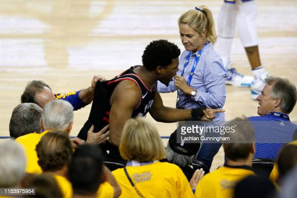 Kyle Lowry of the Toronto Raptors argues with Warriors minority investor Mark Stevens after Lowry chased down a loose ball in the second half against...
