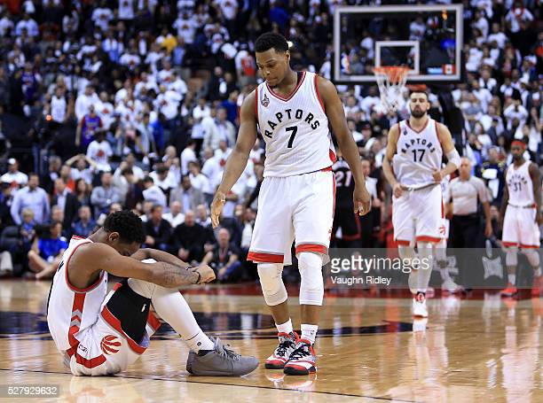 Kyle Lowry of the Toronto Raptors attempts to help DeMar DeRozan up off the floor late in the second half of Game One of the Eastern Conference...