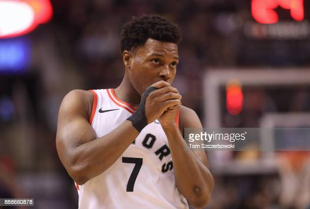 Kyle Lowry of the Toronto Raptors blows on his hands as he looks on against the Charlotte Hornets during NBA game action at Air Canada Centre on...