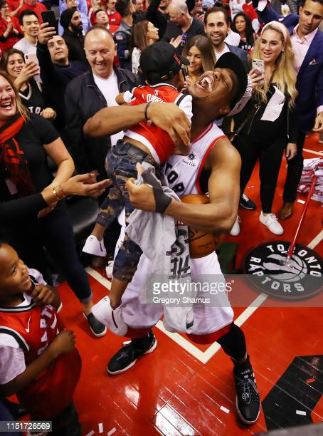 Kyle Lowry of the Toronto Raptors celebrates with his sons Kameron and Karter after defeating the Milwaukee Bucks 10094 in game six of the NBA...