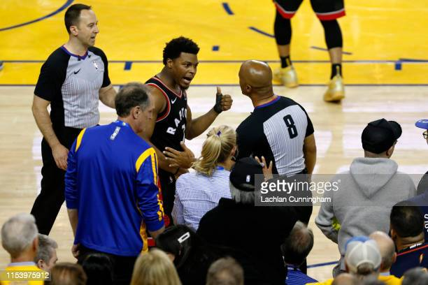 Kyle Lowry of the Toronto Raptors complains to referee Marc Davis after being pushed by Warriors minority investor Mark Stevens in the second half...