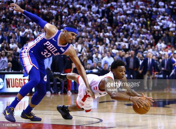 Kyle Lowry of the Toronto Raptors dives for the ball as Tobias Harris of the Philadelphia 76ers defends during Game Two of the second round of the...