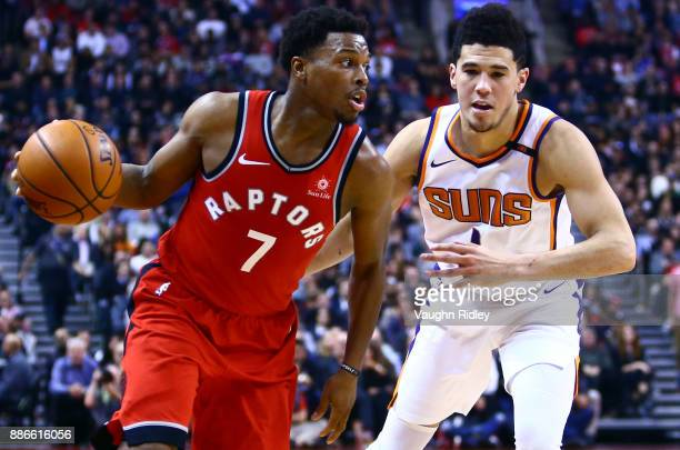 Kyle Lowry of the Toronto Raptors dribbles the ball as Devin Booker of the Phoenix Suns defends during the first half of an NBA game at Air Canada...