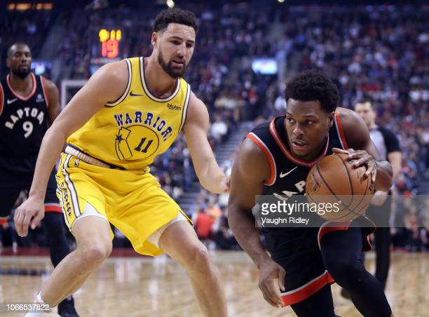 Kyle Lowry of the Toronto Raptors dribbles the ball as Klay Thompson of the Golden State Warriors defends during the first half of an NBA game at...