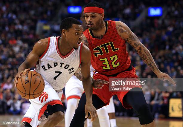 Kyle Lowry of the Toronto Raptors dribbles the ball as Mike Scott of the Atlanta Hawks defends during the first half of an NBA game at Air Canada...