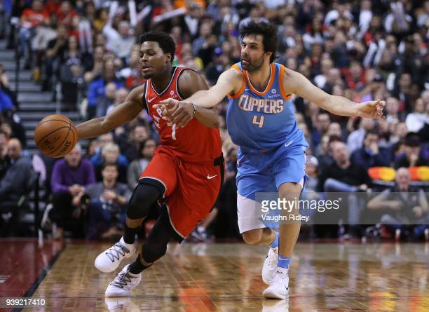 Kyle Lowry of the Toronto Raptors dribbles the ball as Milos Teodosic of the Los Angeles Clippers defends during the second half of an NBA game at...