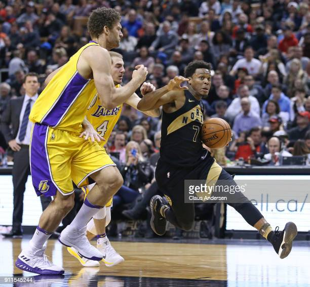 Kyle Lowry of the Toronto Raptors drives against Alex Caruso and Brooks Lopez of the Los Angeles Lakers in an NBA game at the Air Canada Centre on...