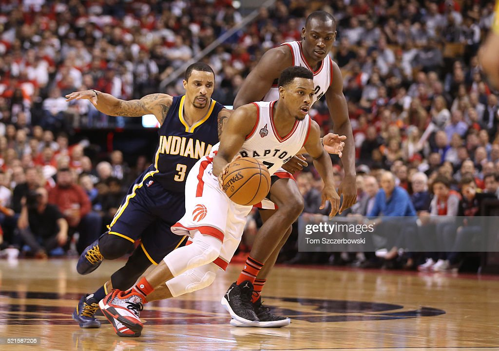 Kyle Lowry #7 of the Toronto Raptors gets a pick from Bismack Biyombo #8 and drives past George Hill #3 of the Indiana Pacers in Game One of the Eastern Conference Quarterfinals during the 2016 NBA Playoffs on April 16, 2016 at the Air Canada Centre in Toronto, Ontario, Canada.