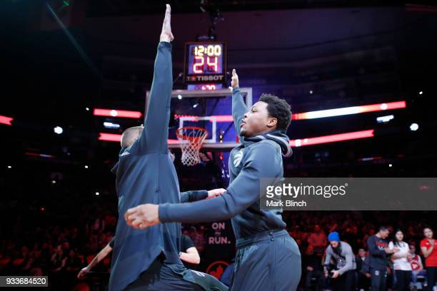 Kyle Lowry of the Toronto Raptors high fives Jonas Valanciunas of the Toronto Raptors before the game against the Oklahoma City Thunder on March 18...