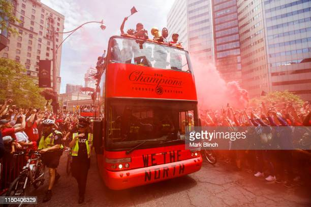 Kyle Lowry of the Toronto Raptors holds the NBA Championship Trophy from the team bus during the Toronto Raptors Championship Victory Parade on June...