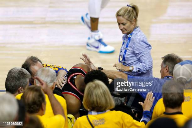 Kyle Lowry of the Toronto Raptors is pushed by Warriors minority investor Mark Stevens after falling into the seats after a play against the Golden...