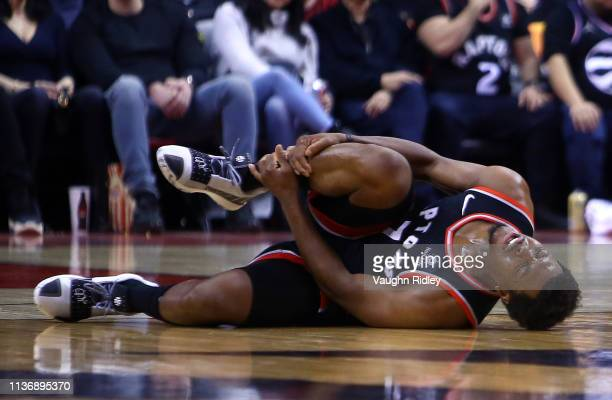 Kyle Lowry of the Toronto Raptors reacts after injuring his right ankle and leaves the game during the second half of an NBA game against the New...