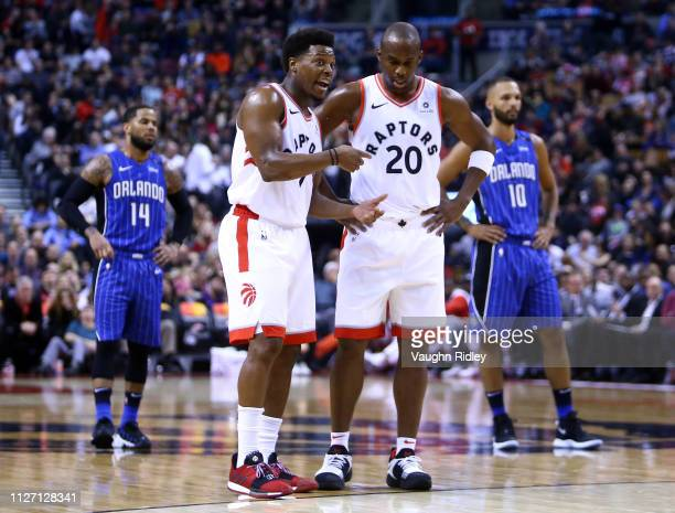 Kyle Lowry of the Toronto Raptors speaks to new teammate Jodie Meeks during the first half of an NBA game against the Orlando Magic at Scotiabank...