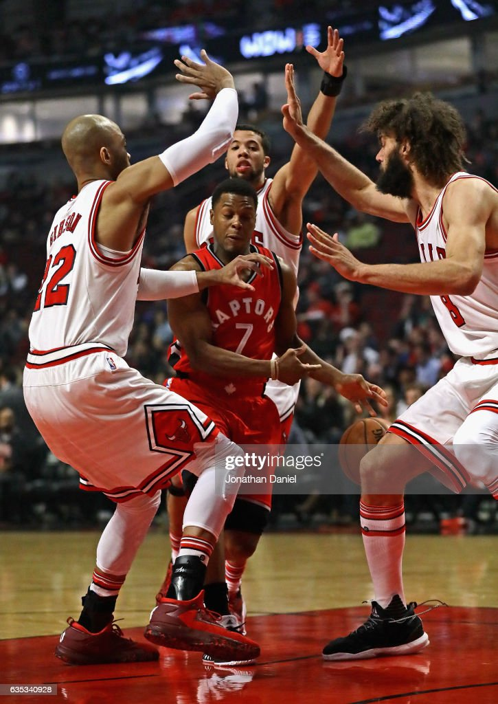 Kyle Lowry #7 of the Toronto Raptors tries to drive between (L-R) Taj Gibson #22, Michael Carter-Williams #7 and Robin Lopez #8 of the Chicago Bulls at the United Center on February 14, 2017 in Chicago, Illinois.