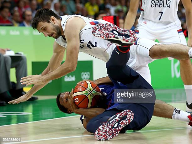 Kyle Lowry of United States fights for a loose ball with Stefan Bircevic of Serbia during the Men's Gold medal game on Day 16 of the Rio 2016 Olympic...