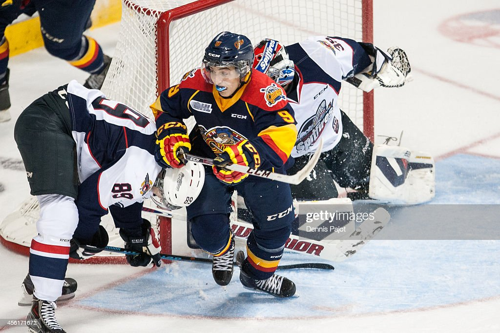 Kyle Maksimovich #9 of the Erie Otters battles against Daniil Vertiy #89 of the Windsor Spitfires on September 26, 2014 at the WFCU Centre in Windsor, Ontario, Canada.