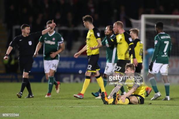 Kyle McFadzean of Burton Albion recovers after being fouled while his teammates hound match referee Tony Harrington to show a second yellow card to...